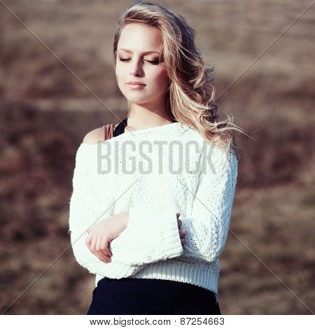 Portrait Of A Beautiful Young Blonde Girl In The White Pullovers