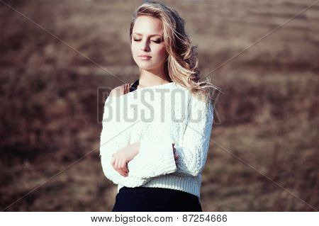 Portrait Of A Beautiful Young Blonde Girl In A Field