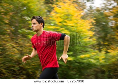 Young man running outdoors in a city park on a fall/autumn day (motion blurred image)