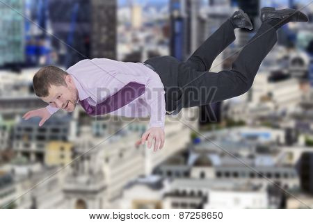 Businessman falling down with modern city in background