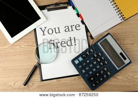 Message You're Fired on clapboard on wooden table, top view
