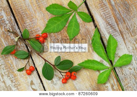 Happy Mother's day card with rowan berries and green leaves on rustic wooden surface