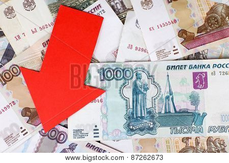 Red arrow on Russian money as depreciation of currency, closeup