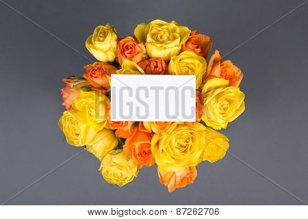 Blank Gift Card And Beautiful Bouquet Of Roses Over Grey