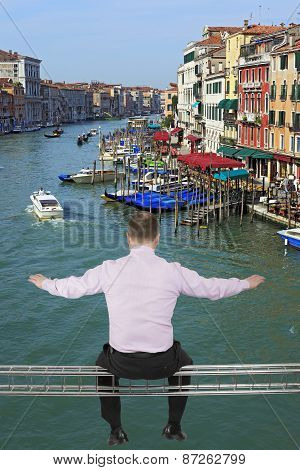Businessman sitting on light metal girder beam with view of Venice, Italy in background