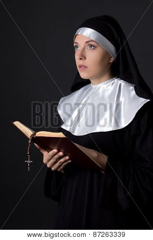 Portrait Of Young Beautiful Woman Nun Reading Bible Over Grey