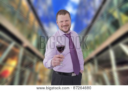 Businessman holding glass of wine with modern shopping mall in background