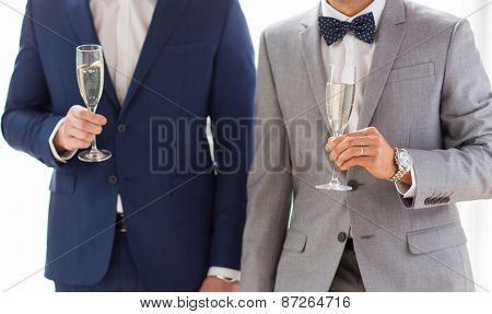 people, celebration, homosexuality, same-sex marriage and love concept - close up of happy married male gay couple in suits and bow-ties drinking sparkling wine from glasses on wedding