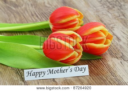 Happy Mother's Day card with red and yellow tulips on wooden surface