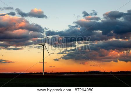 Wind power plant in sunset