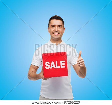 shopping, discount, consumerism, gesture and people concept - smiling man with red sale sigh showing thumbs up over blue background