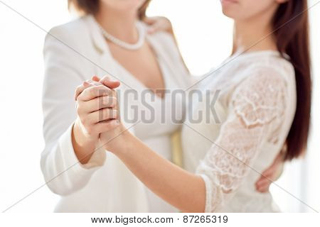 people, homosexuality, same-sex marriage and love concept - close up of happy married lesbian couple dancing