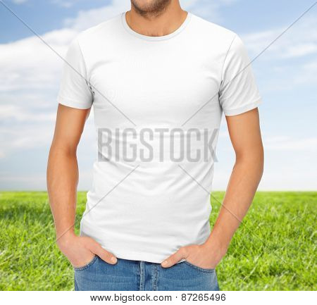 clothing design, advertisement, fashion and people concept - close up of ma in blank white t-shirt over blue sky and grass background