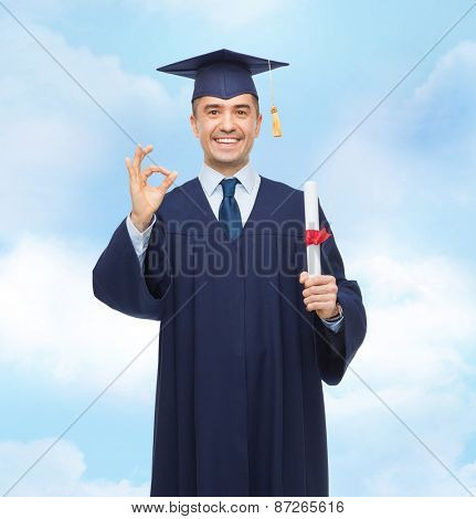 education, graduation, gesture and people concept - smiling adult student in mortarboard with diploma showing ok hand sign over blue sky background