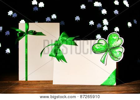 Greeting card for Saint Patrick's Day on wooden table on dark lights background