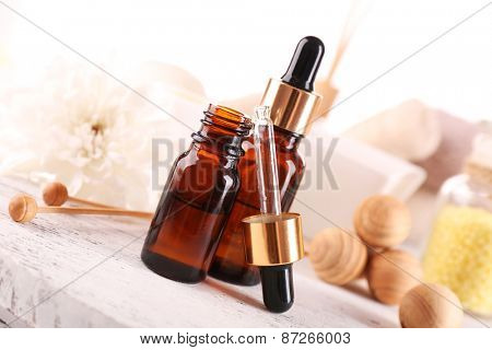 Spa dropper bottles with essence on wooden table, closeup