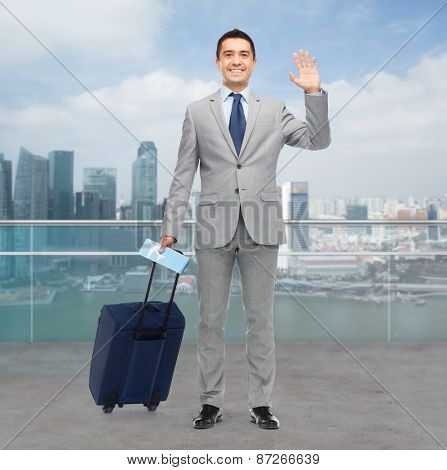 business trip, traveling, luggage and people concept - happy businessman in suit with travel bag and air ticket waving hand over city background