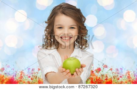 people, children, healthy eating, summer and food concept- happy girl holding green apple over blue sky and poppy field n background