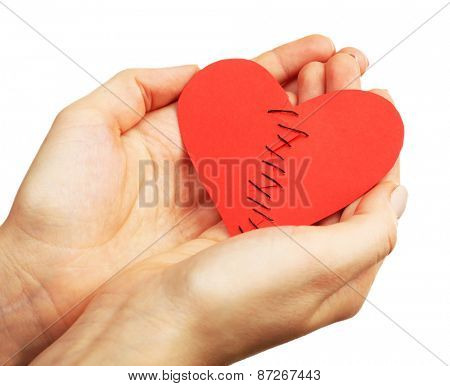 Female hands holding broken heart stitched from two pieces isolated on white
