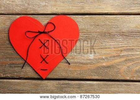 Stitched heart on wooden background
