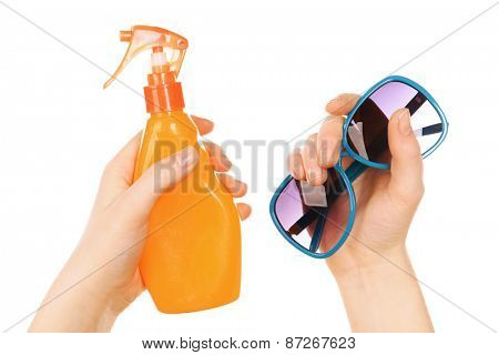 Bottle of suntan spray and sunglasses in female hands isolated on white