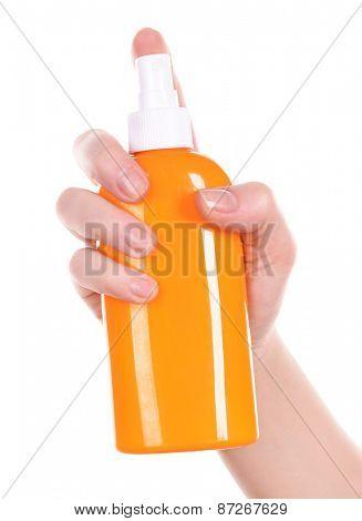 Bottle of suntan spray in female hand isolated on white