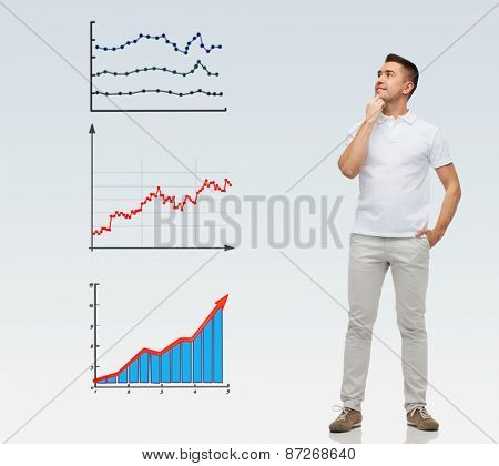 business, statistics, economics and people concept - smiling man with hands in pockets looking up to growing chart over gray background