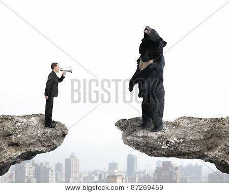 Businessman Yelling At Black Bear On Cliff With Cityscape