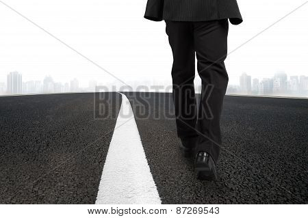 Businessman Walking On Asphalt Road With Urban Scene