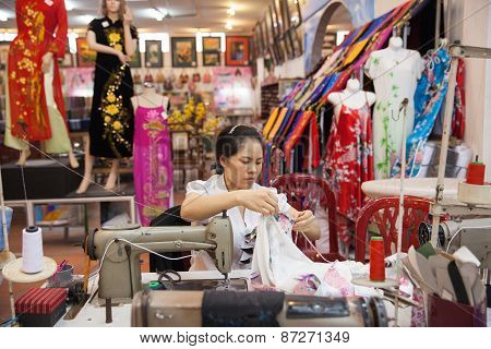Vietnamese tailor woman sews traditional silk dress