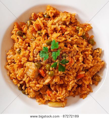 Pilaf with chicken, carrot and green peas on  plate