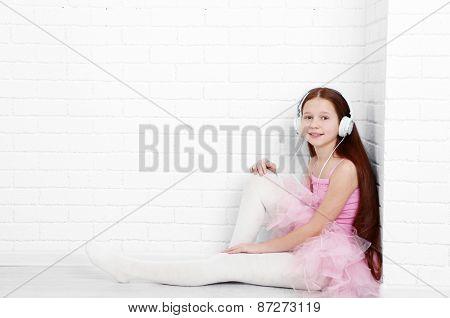 Beautiful little ballerina on  white bricks wall background