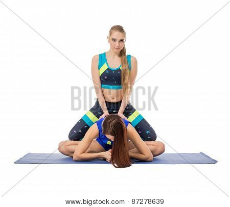Cute girl helps to her friend doing stretching