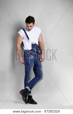 Man in jeans coveralls on gray background