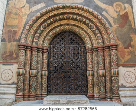 Main gate entrance into the Cathedral of the Assumption in the Kremlin. Highly decorated arches circled by paintings.