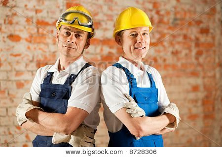 Construction workers standing with folded