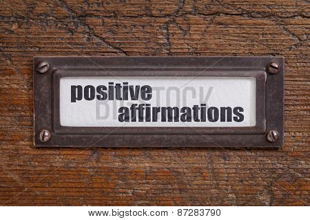 positive affirmations - file cabinet label, bronze holder against grunge and scratched wood