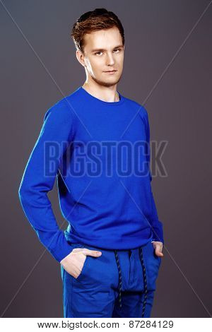 Smiling young man wearing casual clothes posing at studio. Men's beauty, fashion.