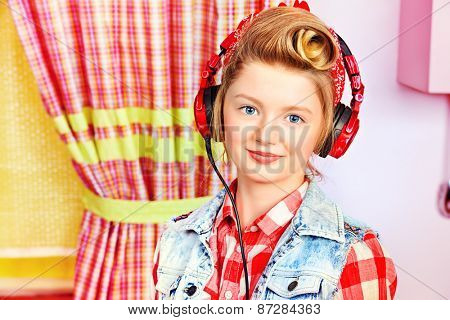 Lovely pin-up girl teenager listening to music in headphones on a pink kitchen. Beauty, youth fashion. Pin-up style.
