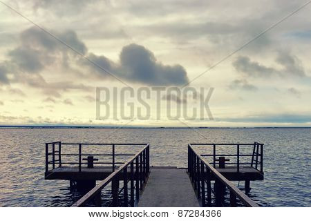 Pier At The Sea On A Background Of Clouds