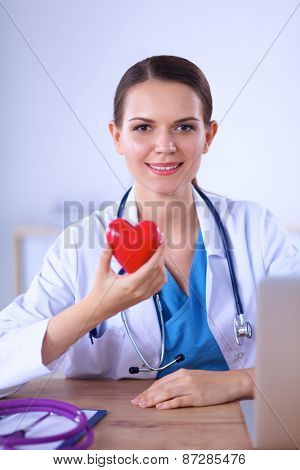 Happy doctor with red heart symbol at desk