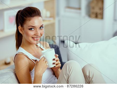 Portrait of oung beautiful woman with a cup on sofa at home