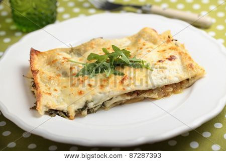 Lasagna with arugula on a served table