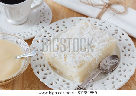 Rice Pudding With Coconut On White Plate With Cup Of Coffee And Condensed Milk On Table