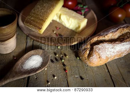 Rustic Bread, Cheese And Salt On A Wooden Table