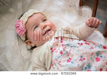 Charming baby girl with diadem lying on his back and laughs