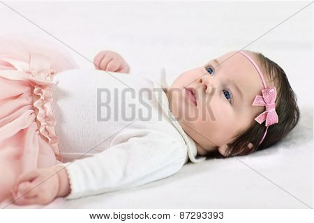 Charming baby girl with diadem lying on his back