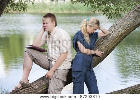 The guy and the girl in quarrel on the bank of the lake