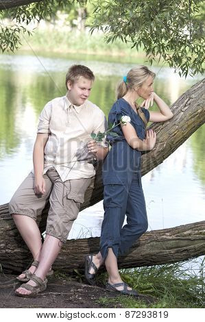Young guy and girl on the nature near lake reconciliation after quarrel