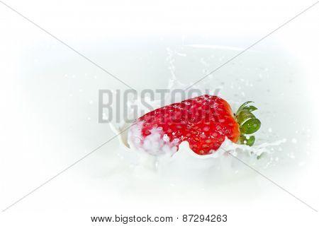 delicious fresh strawberry falling into splashing milk